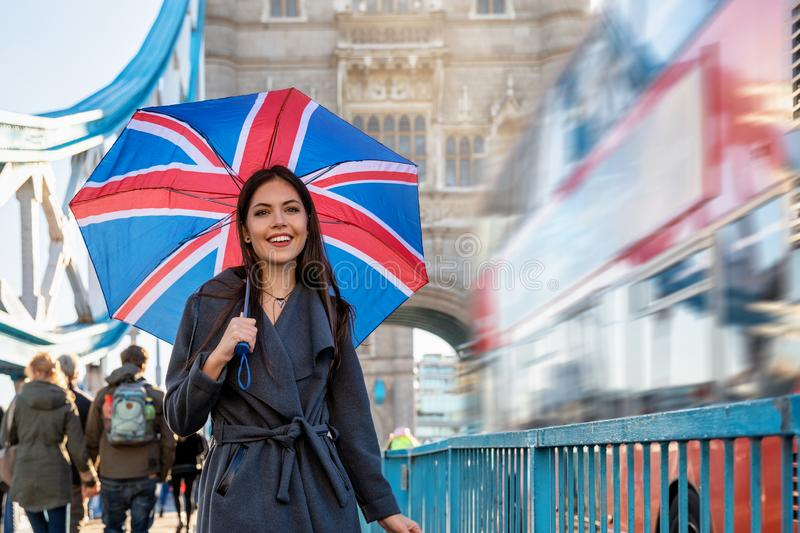 Woman with a British flag umbrella walks on the Tower Bridge. Pretty London traveler woman with a British flag umbrella walks on the Tower Bridge during a stock photo