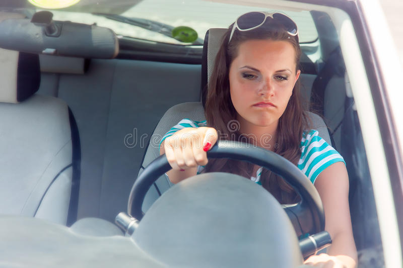 Woman and broken car. Young woman is trying to turn the broken car on stock photo