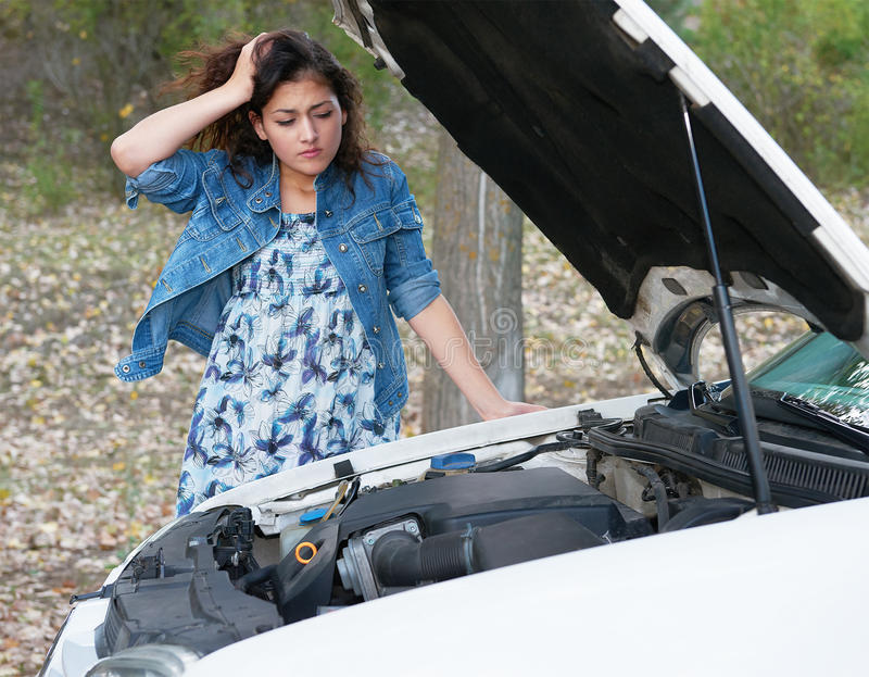 Woman with broken car inspecting engine royalty free stock image