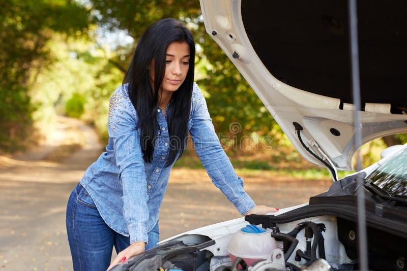 Woman with a broken car. Sad young woman with a broken car stock photos