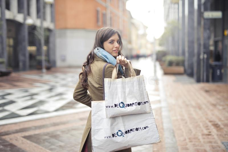 Woman in Brown Coat Carrying Two White Tote Bags stock photo