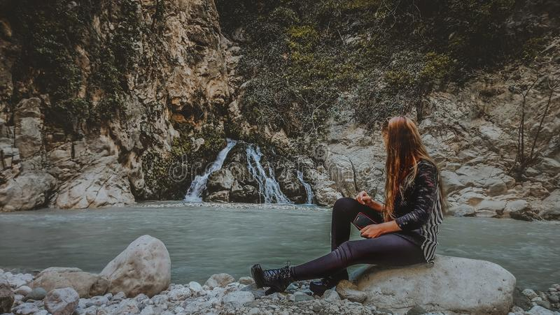 Woman With Brown Hair in Black Jacket Sitting on Rock Near Body of Water stock photography