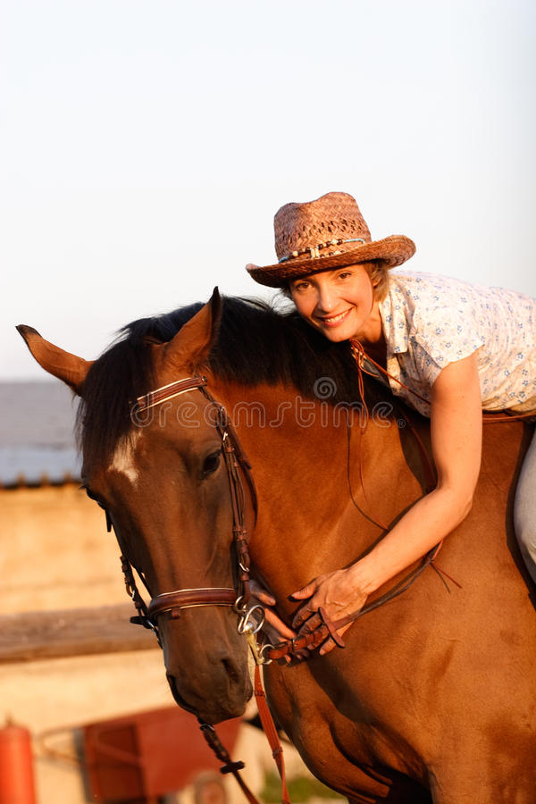 Woman on brown horse stock image