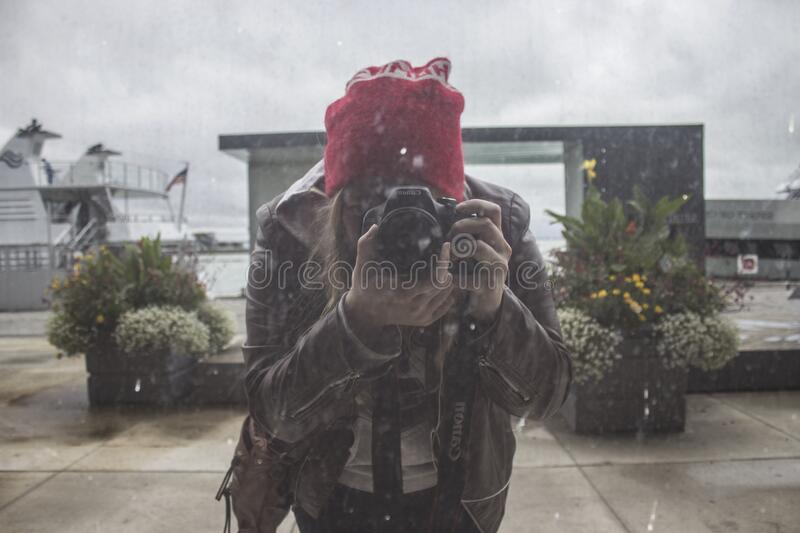 Woman In Brown Leather Jacket And Red Knit Cap Using Black Dslr Camera Free Public Domain Cc0 Image