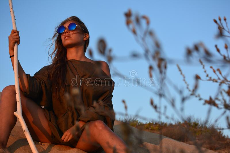 Woman in Brown Shirt Sitting Near Green Plant Under Clear Blue Sky royalty free stock photo