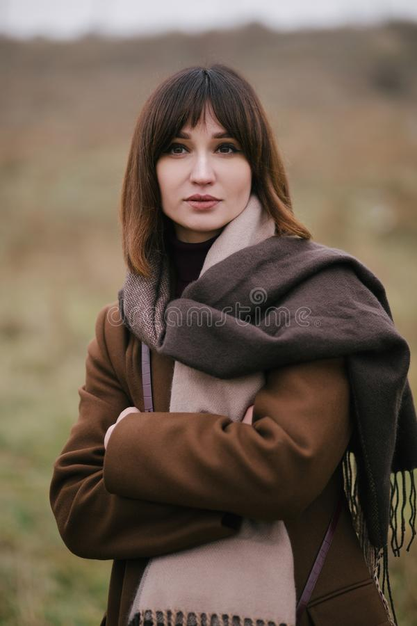Woman in brown stylish cashmere posing on autumn background. Young beautiful woman in brown stylish cashmere posing on the autumn landscapes background royalty free stock photo