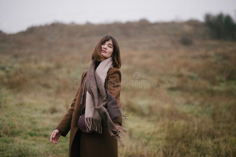 Woman in brown stylish cashmere posing on autumn background. Young beautiful woman in brown stylish cashmere posing on the autumn landscapes background royalty free stock photos