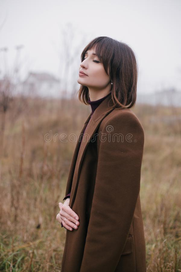 Woman in brown stylish cashmere posing on autumn background. Young beautiful woman in brown stylish cashmere posing on the autumn landscapes background stock images