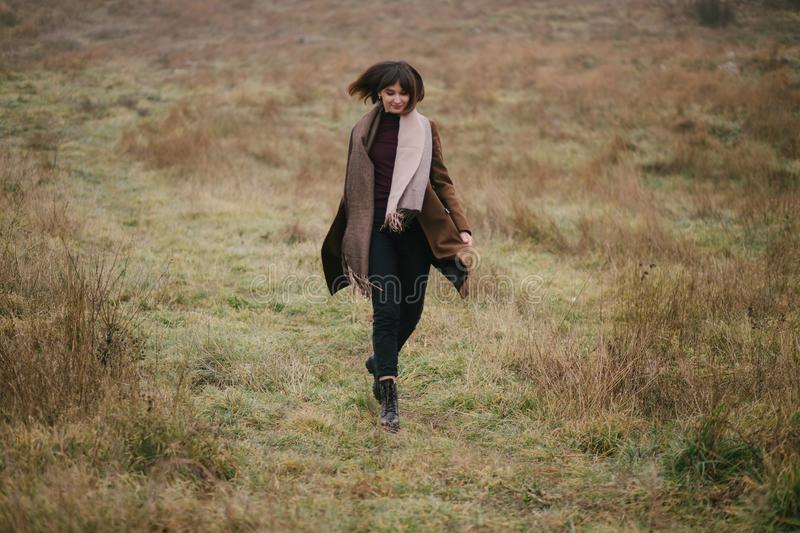 Woman in brown stylish cashmere posing on autumn background. Young beautiful woman in brown stylish cashmere posing on the autumn landscapes background stock photo