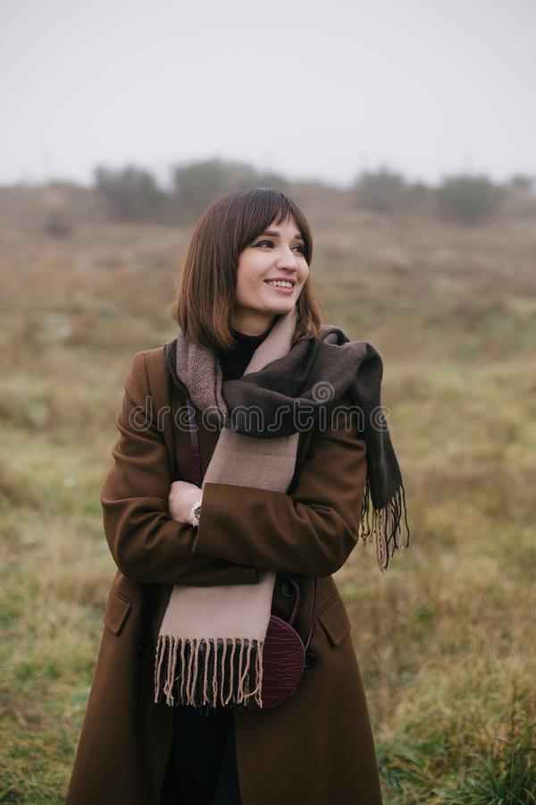 Woman in brown stylish cashmere posing on autumn background. Young beautiful woman in brown stylish cashmere posing on the autumn landscapes background stock photos
