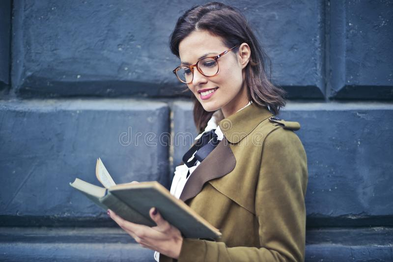 Woman In Brown Suede Peacoat Reading A Book stock images