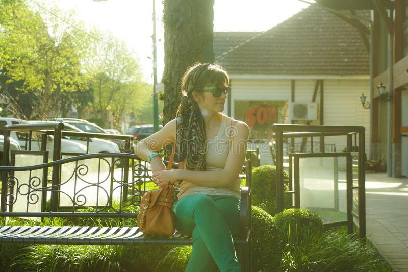 Woman in Brown Tank Top Sitting on Black Bench Beside Tree stock photography
