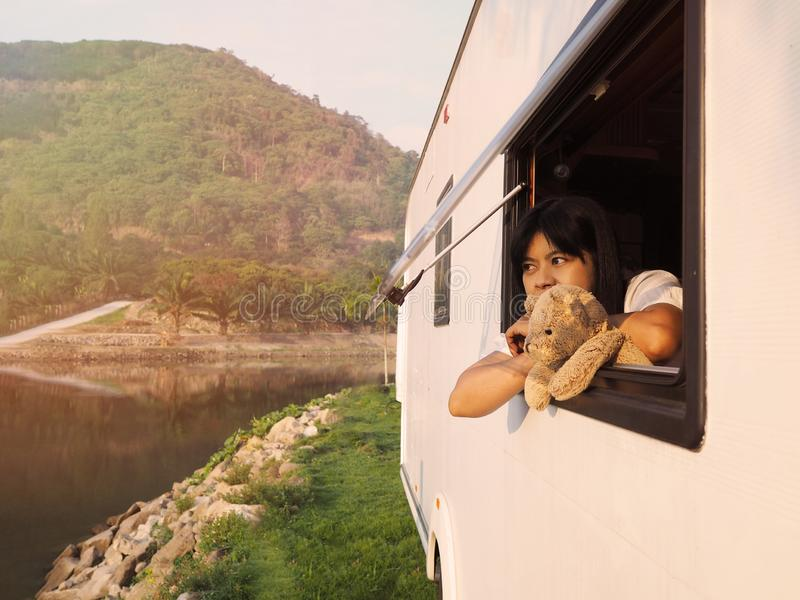 Woman and brown teddy bear looking out of camper van window stock photos