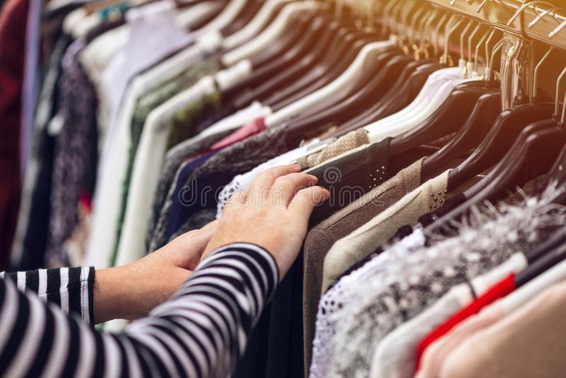 Woman browsing through clothing at second hand street market. Selective focus on clothes royalty free stock photo