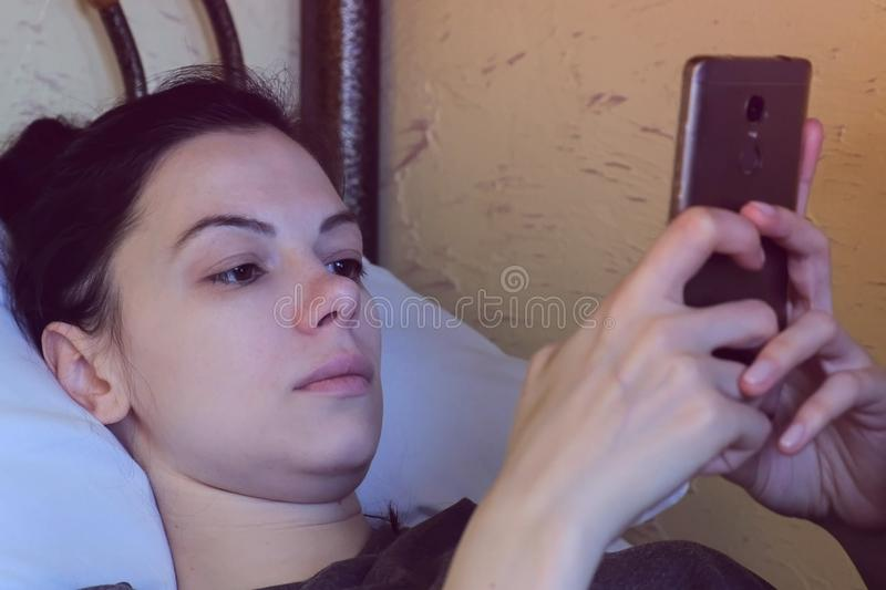Woman is browsing internet in mobole phone, Face close-up, side view. stock photos