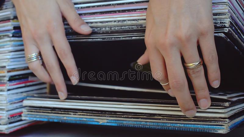 Woman Browsing Vinyl. Close Up Of Female Adult Hands Wearing Various Rings Browsing Through Vinyl Records stock images