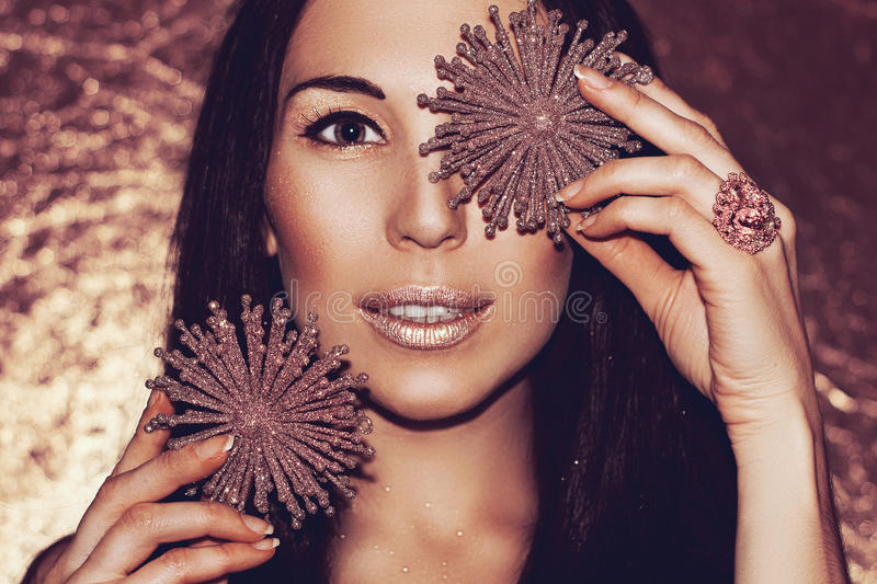Woman brunette with Christmas decorations bronze snowflakes. royalty free stock image