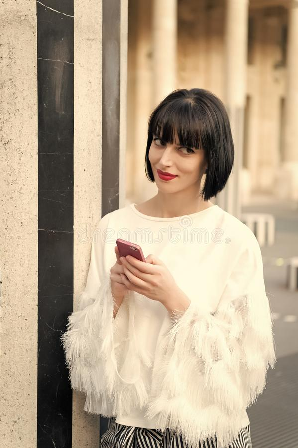 Woman with brunette hair hold mobile phone. Woman with red lips use smartphone in paris, france. Beauty girl with royalty free stock image