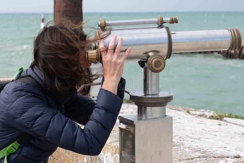 Woman brunette looking through coin operated binoculars at seaside ocean beach stock image