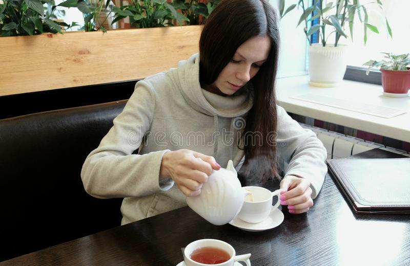 Woman brunette pours tea from a teapot kettle into a cup. stock image