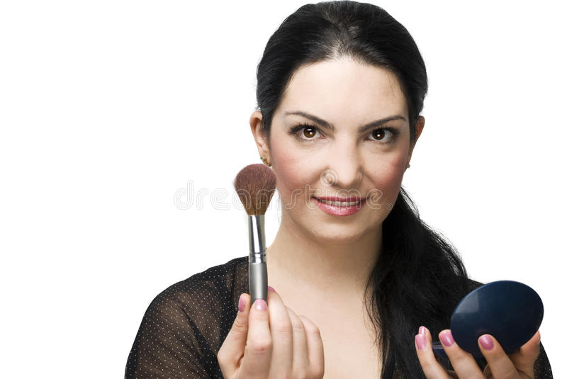 Woman with brush for blush and mirror royalty free stock photography