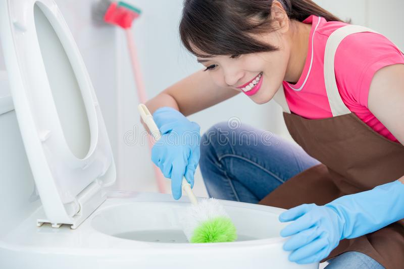 Woman brush the toilet stock image