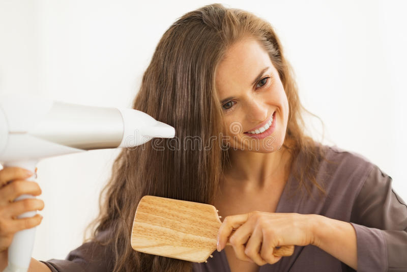 Woman brushing and blow drying hair in bathroom. Happy young woman brushing and blow drying hair in bathroom stock image