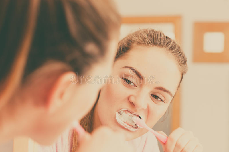 Woman brushing cleaning teeth in bathroom. Woman brushing cleaning teeth. Girl with toothbrush in bathroom looking at mirror. Oral hygiene. Filtered photo stock photo