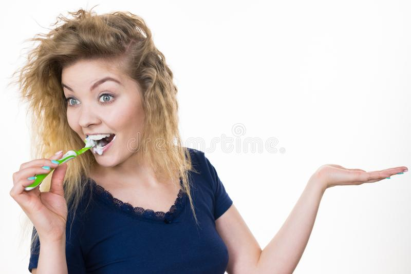 Woman brushing teeth holds open hand stock image