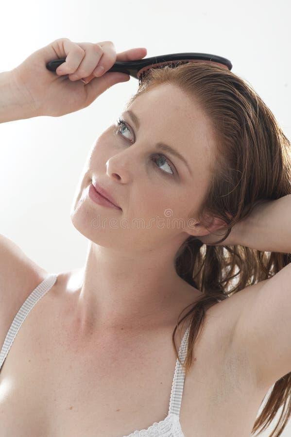 Woman brushing hair royalty free stock photography