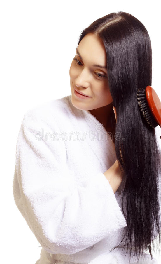 Woman brushing her hair. Young woman brushing her long, dark hair, wearing a white robe; isolated on a white background royalty free stock photography