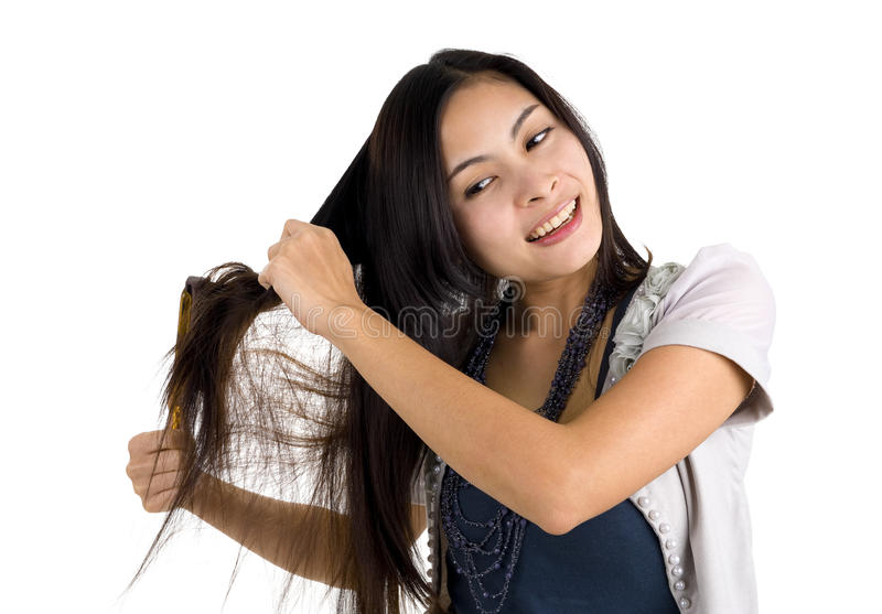 Woman brushing her hair. Pretty woman brushing her long hair, isolated on white background royalty free stock image