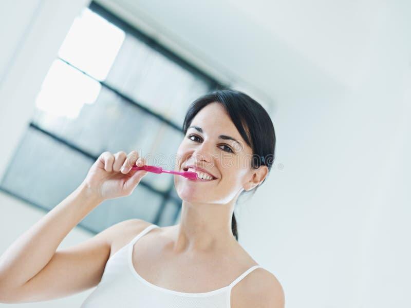 Woman brushing teeth. Woman in bathroom brushing teeth. Copy space stock image