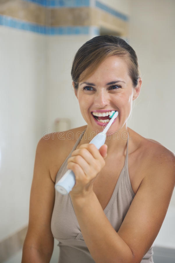 Woman brushing teeth with electric toothbrush. Happy woman brushing teeth with electric toothbrush royalty free stock photo