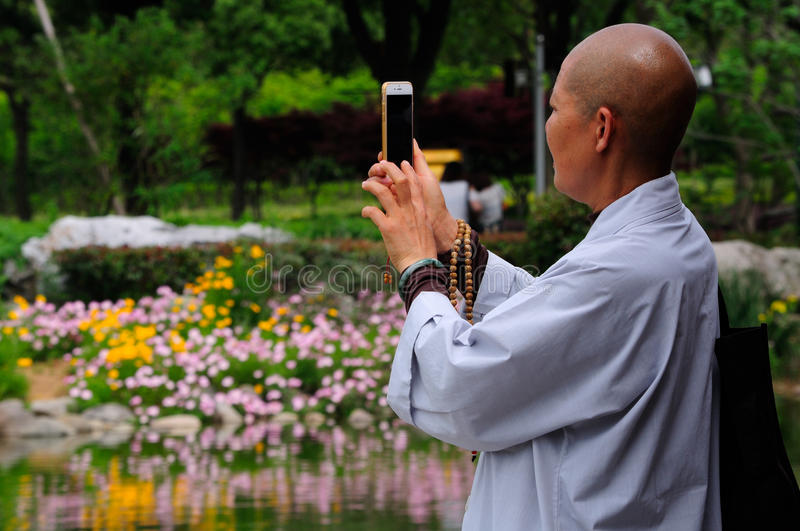 Woman Buddhist Monk. A bald chinese woman buddhist monk holding prayer beads while snapping a picture with her Apple I phone at Lingshan Scenic area in Wuxi