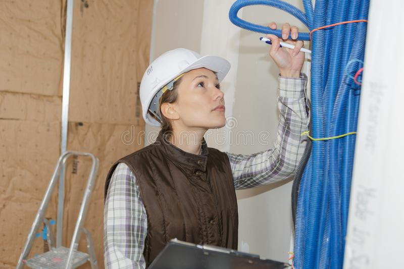 Woman builder fixing heating system royalty free stock photography