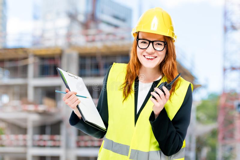 Woman builder in protective clothes at construction site walkie-talkie stock photos
