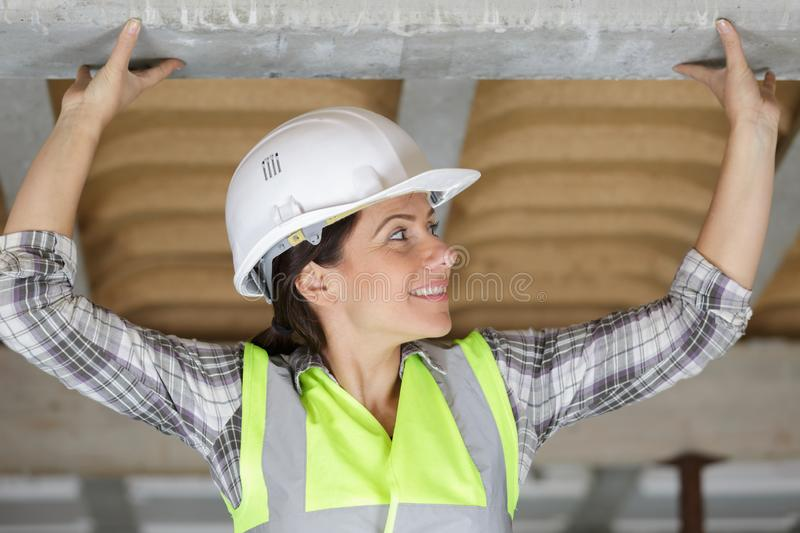 Woman builder working on roof stock photo