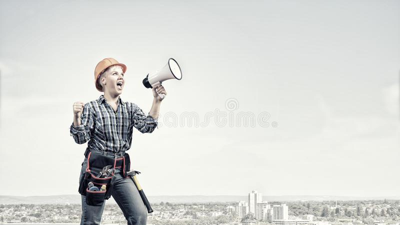 Woman builder. Young woman in hardhat screaming in megaphone stock photos