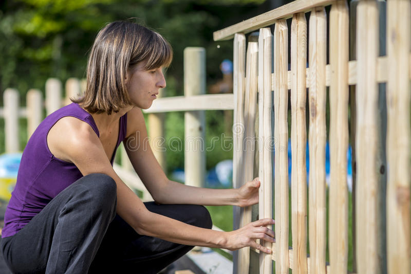 Woman building a garden fence. Placing an upright wooden slat in position to be hammered into place in a close up side view of her kneeling royalty free stock photography