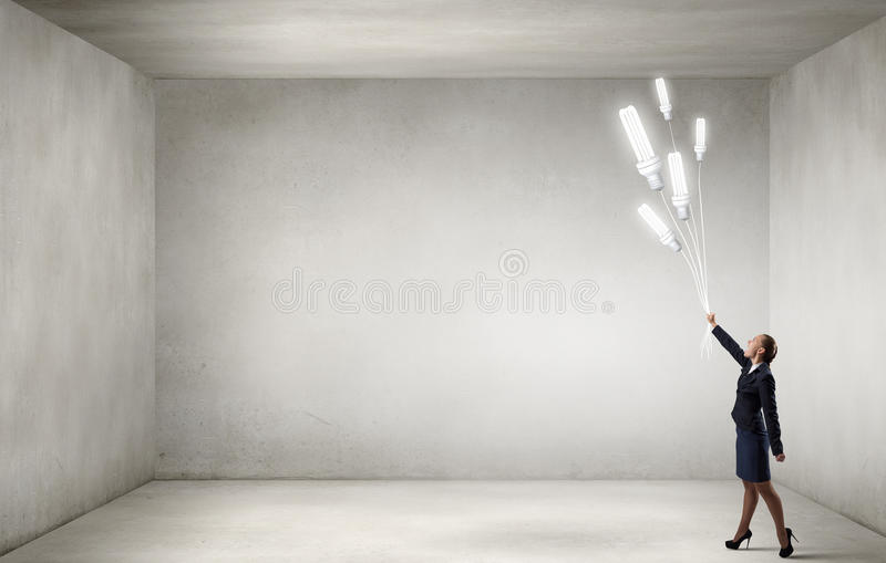 Woman with bulb balloon. Businesswoman holding in hand bunch of light bulb balloons stock photography