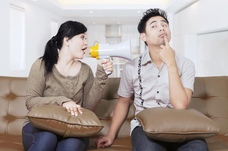 Woman with bullhorn screaming at man. Angry young women screaming at a men with a bullhorn while sitting on the couch at home stock image