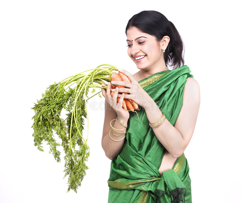 Woman with a bunch of carrots. Young asian woman of indian origin with a bunch of carrots stock photos