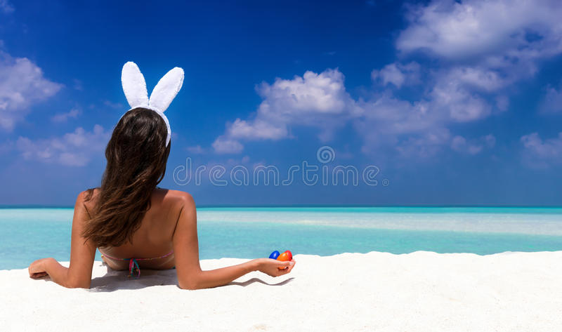 Woman with bunny ears and colorful easter eggs. On a tropical beach in the Maldives stock photography