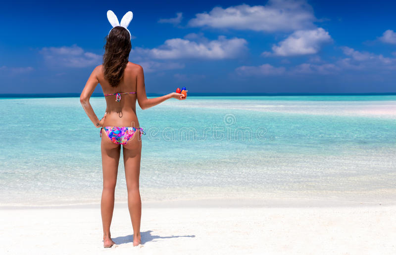 Woman with bunny ears and easter eggs. On tropical beach stock photo