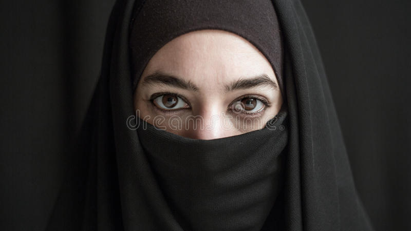 Woman in burka. Woman wrapped in burka over dark background stock photos