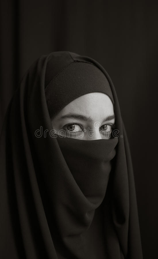 Woman in burka. Woman wrapped in burka over dark background royalty free stock photo