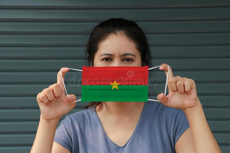 A woman with Burkina Faso flag on hygienic mask in her hand and lifted up the front face on dark green background. Tiny Particle. Or virus corona or Covid 19 royalty free stock photo