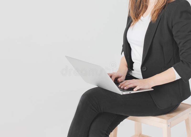 Woman business lady student in black suit working at laptop on grey background isolated stock images