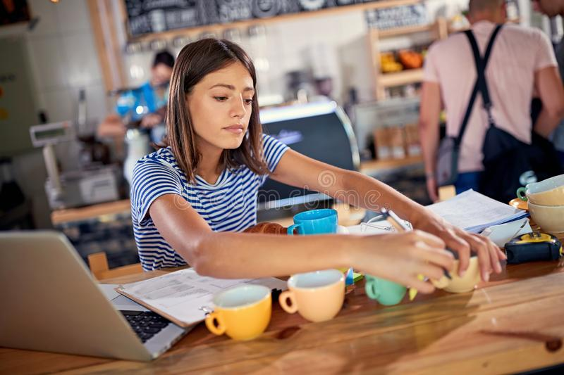 Woman business owner in coffee shop working. Young women business owner in coffee shop working royalty free stock image